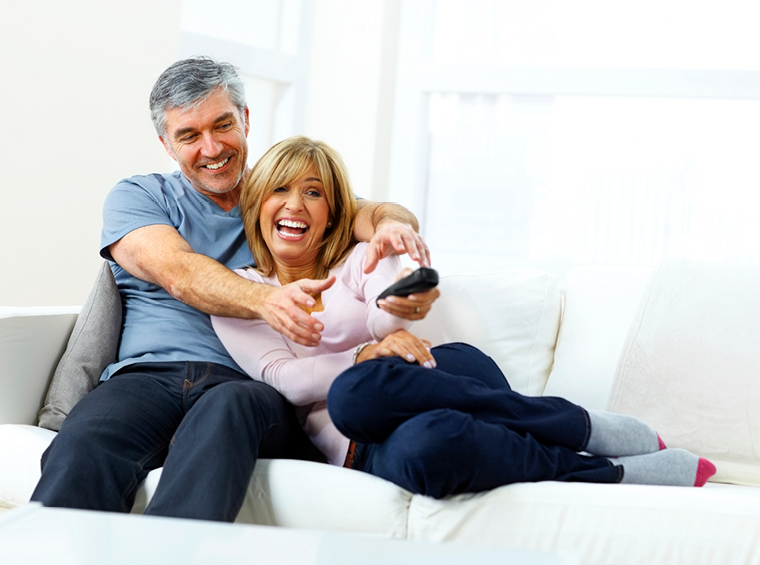 Couple laughing while watching TV