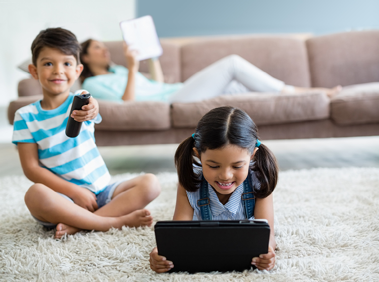 Happy kids watching TV on devices